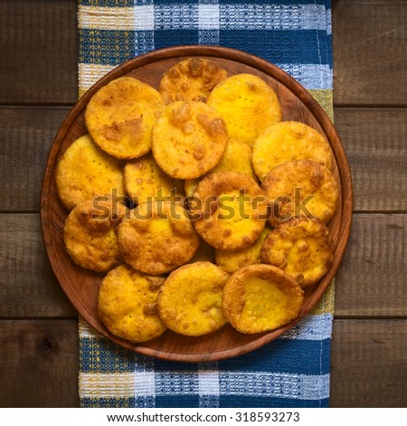 Traditional Chilean Sopaipilla fried pastry made with mashed pumpkin in the dough, served on wooden plate, photographed overhead on wood with natural light - stock photo