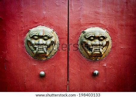 Traditional Chinese ancient architecture door red door and golden lion. - stock photo