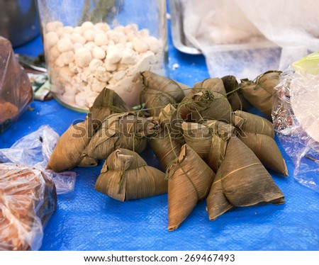 Traditional Chinese food - sticky rice wrapped in bamboo Leaves, eaten in late spring for the dragon boat festival. Here offered in outdoor Chinese market. - stock photo