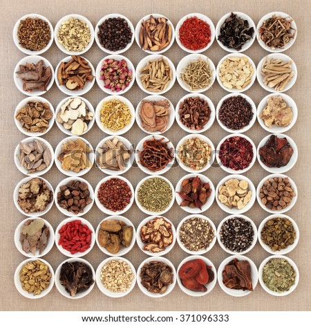 Traditional chinese herbal medicine ingredients in white china bowls over hessian background. - stock photo
