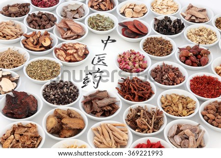 Traditional chinese medicinal herb ingredients with calligraphy on rice paper. Translation reads as chinese herbal medicine.  - stock photo