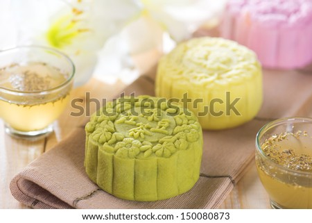Traditional Chinese mid autumn festival food. Snowy skin mooncakes.  The Chinese words on the mooncakes is green tea with red bean paste, noble delight and lotus paste, not a logo or trademark. - stock photo