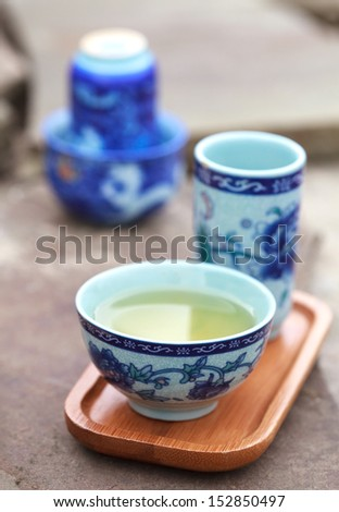 Traditional chinese tea ceremony accessories (tea couple) on the stone table, selective focus on cup  - stock photo