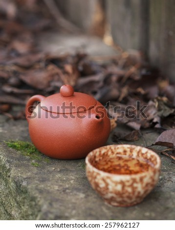Traditional chinese tea ceremony accessories (tea pot and tea cup) on the old stone table, selective focus on the tea pot. Toned - stock photo