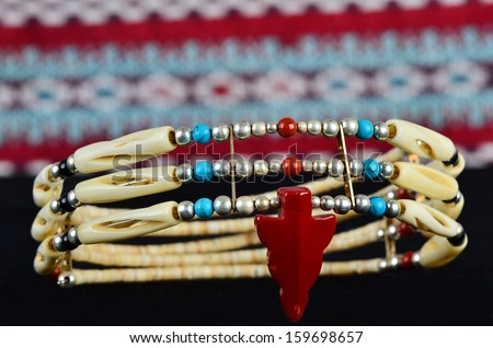 Traditional choker necklace of bone, coral, silver and turquoise in high contrast setting.  Artifact of cultural Native American heritage. Closeup in Selective Focus. - stock photo