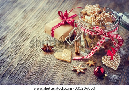 Traditional christmas cookies with icing, festive vintage table decoration with gift box copy space - stock photo