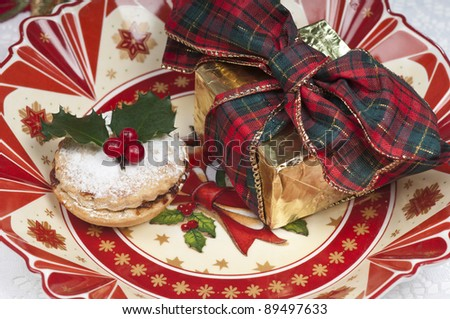 Traditional Christmas English mincepie decorated with icing sugar and holly with berries.  On an attractive  old fashioned cream and red plate. - stock photo
