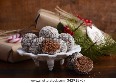 Traditional Christmas Rum Ball candy spotlighted in festive setting with rustic style gifts and decorations on dark vintage wood background, closeup.  - stock photo