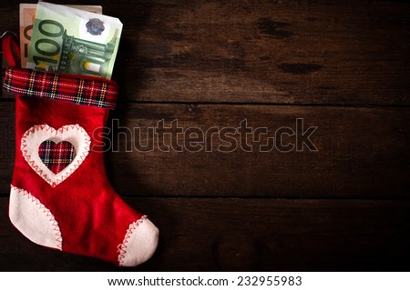 Traditional Christmas sock with the money on wooden wall with blank space  - stock photo