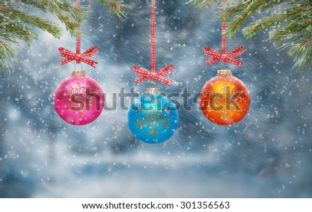Traditional Christmas Tree Decorations hanging from a tree branch with a snow scene background. - stock photo