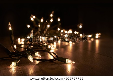 Traditional Christmas Tree lights lying on a wooden floor. - stock photo