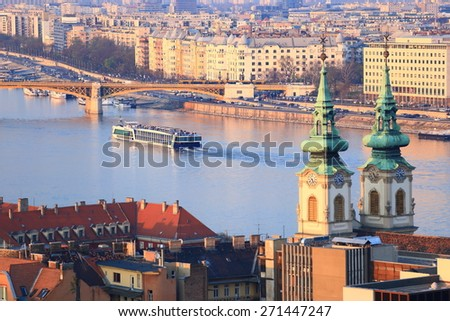 Traditional church towers and tourist boats on Danube river, Budapest, Hungary - stock photo