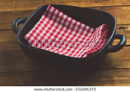 traditional clay pottery pot for kitchen wich red napkin on the wooden table. toning - stock photo