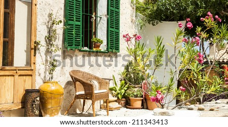Traditional courtyard with chairs and a lot o flowers in old village in Mallorca island, Spain - stock photo