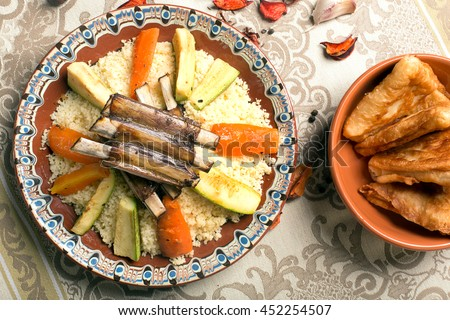 Traditional couscous dish with lamb ribs and vegetables. Top view. The image is describing moroccan culture - stock photo