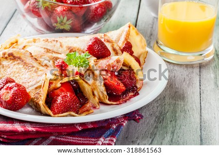 Traditional crepes served with strawberries on a plate - stock photo