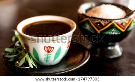 Traditional cup of Ethiopian coffee served with Rue leaf - stock photo