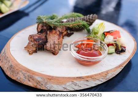 Traditional delicious kebab, meat with tomatoes sauce served on wooden dish. Rustic style, picnic bbq gourmet. - stock photo