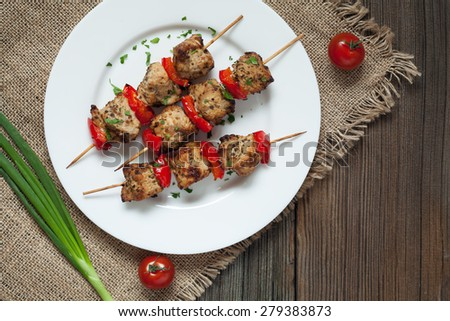 Traditional delicious turkey kebab skewer barbecue meat with tomatoes and green onion on white dish. Wooden vintage background. Rustic style, natureal light. - stock photo