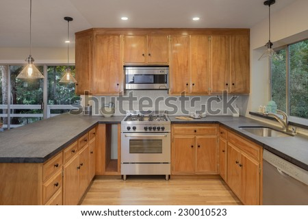 Traditional designed kitchen with wooden cabinets and granite - stock photo