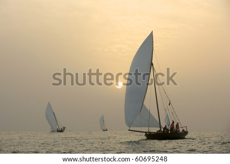Traditional Dhows sailing in the Arabian Gulf, off Dubai, at sunset. - stock photo