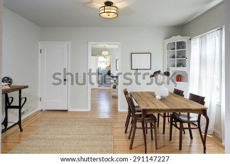 Traditional dining room with wooden table with chairs and built ins next to kitchen. - stock photo