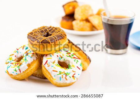traditional donuts of chocolate and vanilla in front slightly out of focus and another plate of covered donuts in background next to coffee cup - stock photo