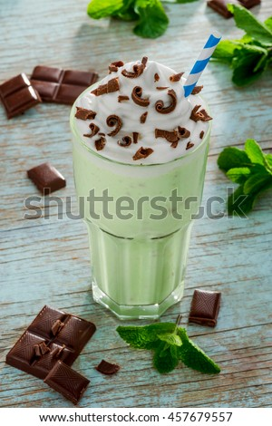 Traditional drink from America for thirsty people. Organic products for tasty recipe of mint milkshake decorated with leaves of this plant, chocolate chips and the straw. - stock photo