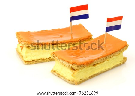 """Traditional Dutch pastry called """"tompouce"""" with a Dutch flag toothpick especially produced for  Queens day on april 30th in Holland on a white background - stock photo"""