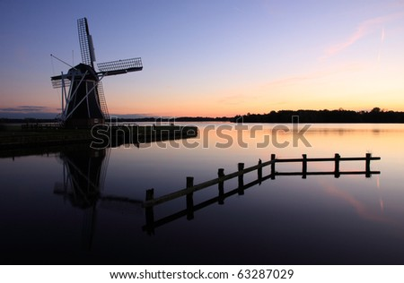Traditional Dutch windmill at a lake during a cold, autumn sunset. - stock photo
