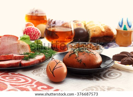 Traditional easter dinner set with sliced meat, bread with herbs, handmade colored eggs, chocolates, easter cake and glasses of juice on colorful tablecloth, horizontal view - stock photo