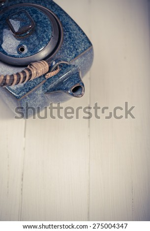 traditional eastern teapot  on wooden desk - stock photo