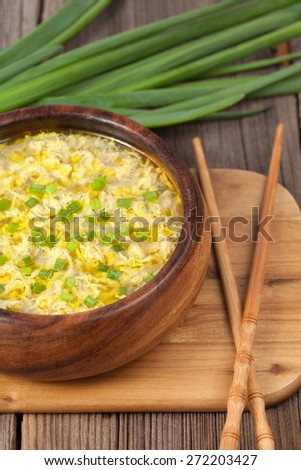 Traditional egg flower soup, tasty asian lunch with food sticks and green onion in wooden bowl on vintage background - stock photo