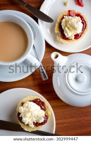 Traditional English afternoon tea of scones with clotted cream and jam, along with a cup of hot tea. - stock photo