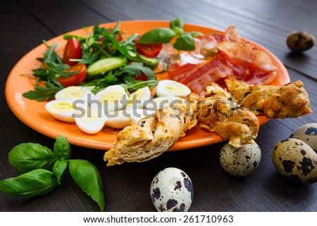 Traditional english breakfast egg, bacon, salad, homemade bread and basil - stock photo