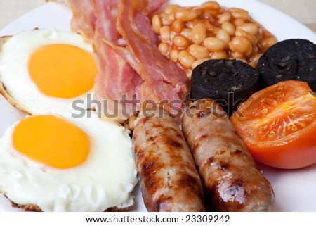 Traditional english breakfast - egg, sausages, beans, bacon and black pudding - stock photo