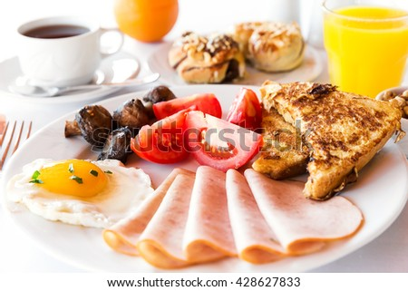 Traditional english breakfast with egg, bacon, mushrooms and tea - stock photo