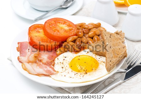 Traditional English breakfast with fried eggs, bacon, beans and toast close-up - stock photo