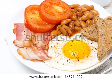 Traditional English breakfast with fried eggs, bacon, beans and toast on the plate, close-up - stock photo