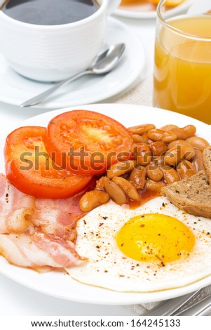 Traditional English breakfast with fried eggs, bacon, beans, coffee and juice, close-up - stock photo