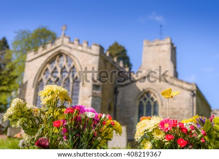 Traditional English church with graveyard on a sunny day - stock photo