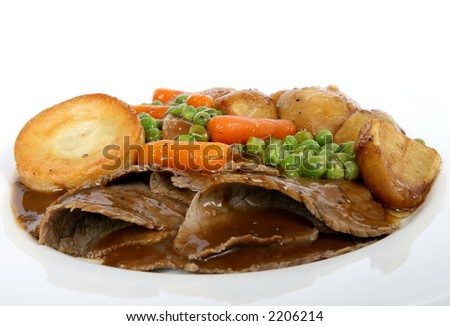 Traditional English Sunday roast with Yorkshire pudding and summer vegetables macro close up isolated on white - stock photo