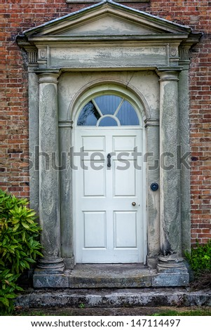 Traditional English victorian front door. Surrounded by  double columns. - stock photo