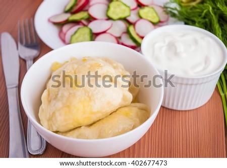 "Traditional European rustic dish ""vareniki"" (pierogi) in a white bowl with sour cream - stock photo"