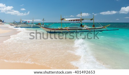 traditional filipino asian ferry taxi tour boats on puka beach in tropical boracay island at philippines - stock photo