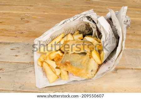 Traditional fish and chips wrapped in a newspaper cone - stock photo