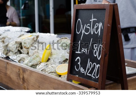 Traditional fish market stall full of fresh shell oysters soft focus or de focus - stock photo