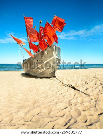 Traditional fisherman boat on a sandy shore of the Baltic Sea. Baabe willage, island Rugen, Germany - stock photo
