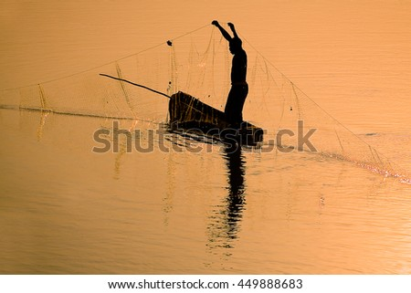 Traditional fisherman casting a net at sunset - stock photo