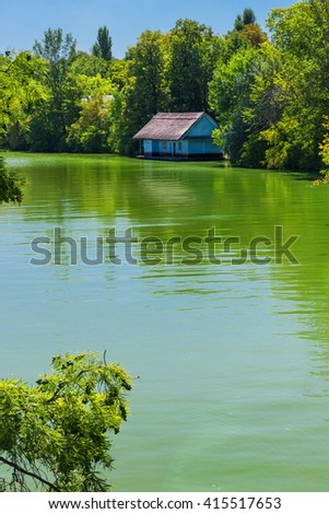 Traditional fisherman wooden house near river and covered by trees - stock photo